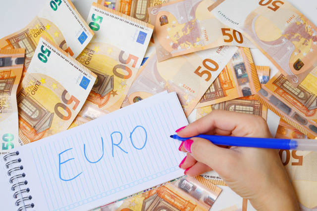 Woman hand writing Euro, 50 Euro banknotes background