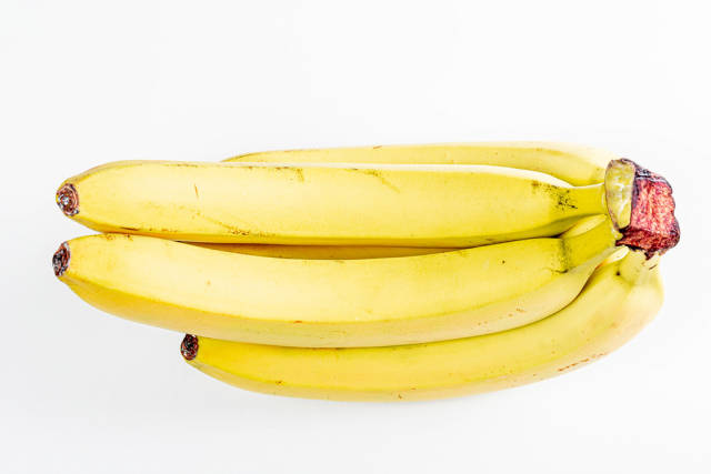 A branch of ripe bananas on a white background