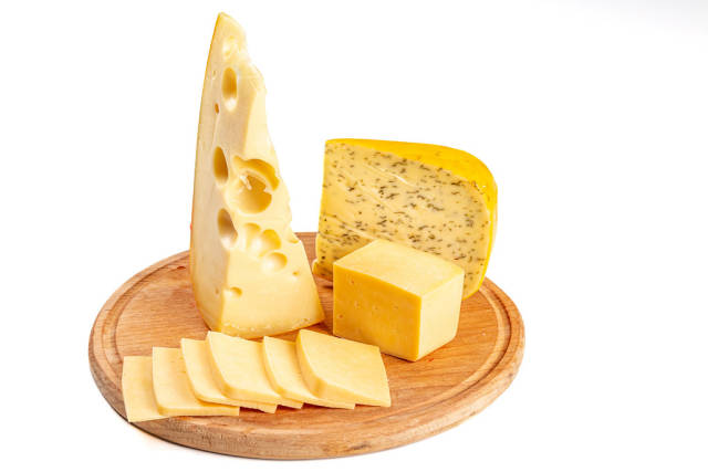 Set of different delicious cheeses on a round wooden kitchen board