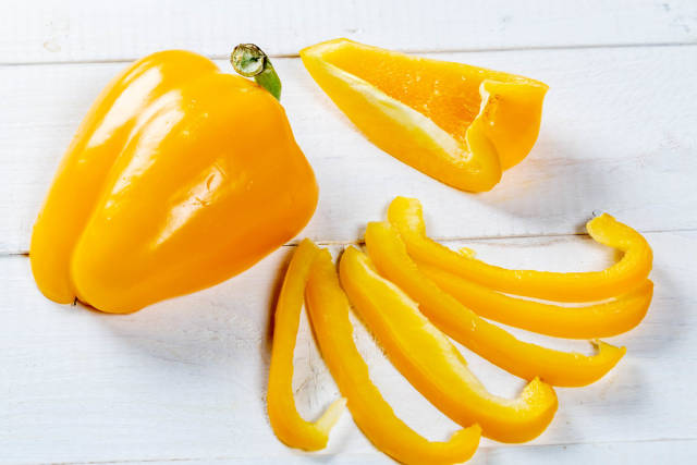 Fresh orange bell pepper on a white wooden background