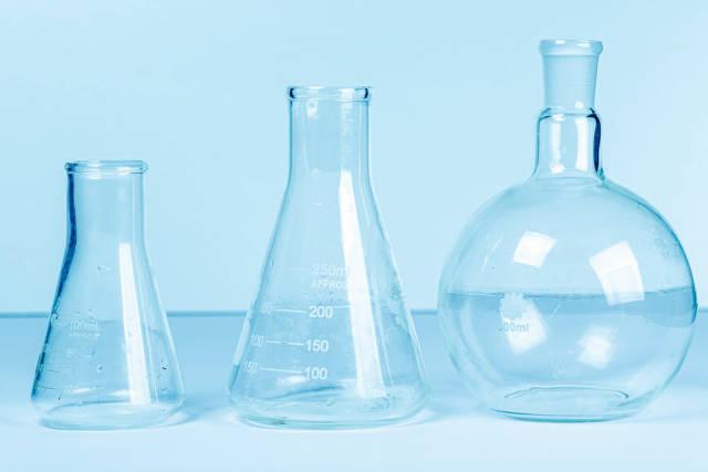 Empty flasks on a light blue background. Laboratory glassware