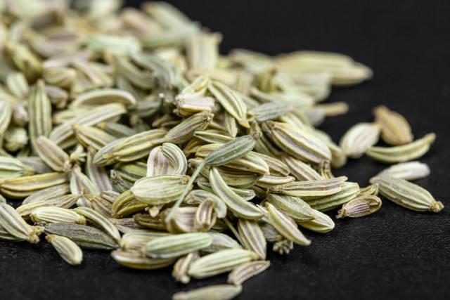 Green fennel seeds on black background, close up