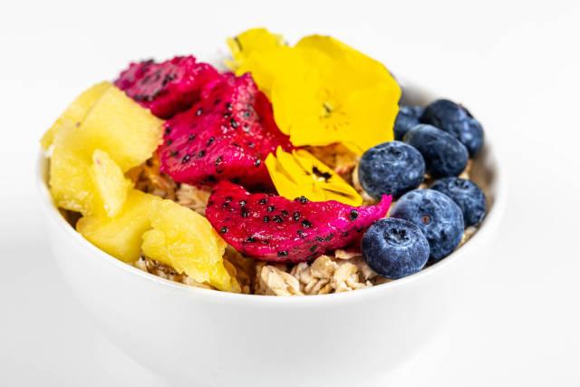 Oatmeal porridge with fresh fruit and yellow flowers