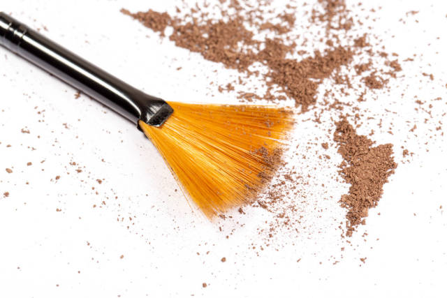 Close-up of a make up powder and a brush on white background