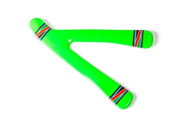 Aufnahme von oben. Grüner Bumerang aus Kunststoff auf weißem Hintergrund