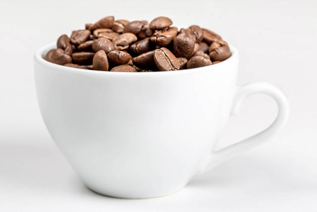A white Cup full of fried coffee beans