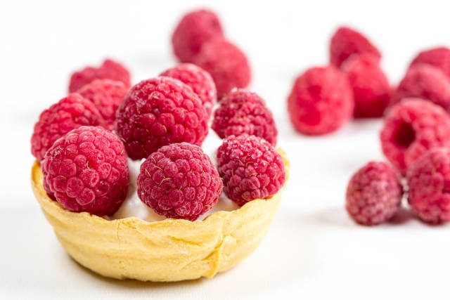 Waffle basket with whipped cream and fresh raspberries