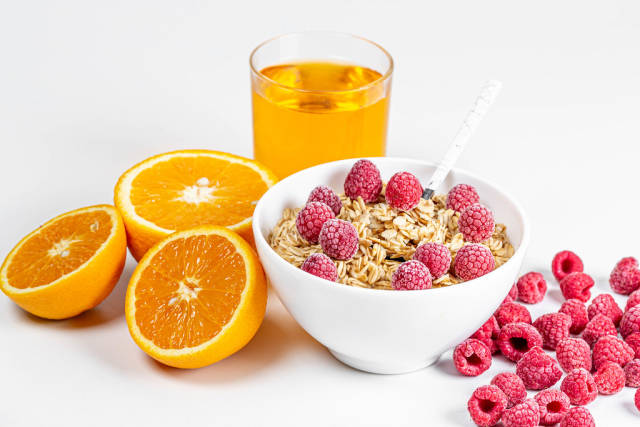 Oatmeal with raspberries, fresh oranges and a glass of juice