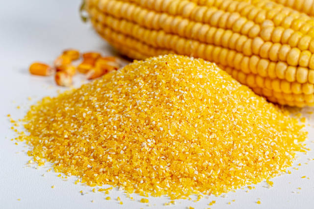 Close-up, a pile of corn grits on white