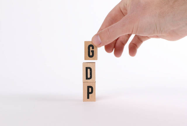 Man hand with wooden blocks with the word GDP on white background