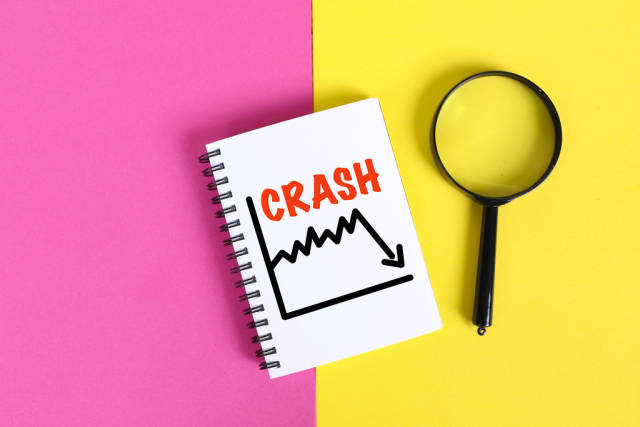 Financial crash concept with notebook and magnifying glass on colorful background