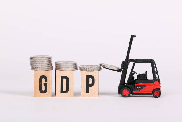 Red forklift lifting coins on top GDP text
