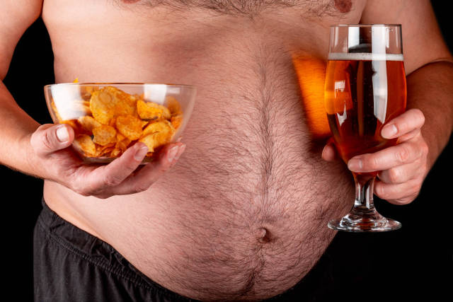 A bowl of chips and light beer in mens hands against the background of a large belly