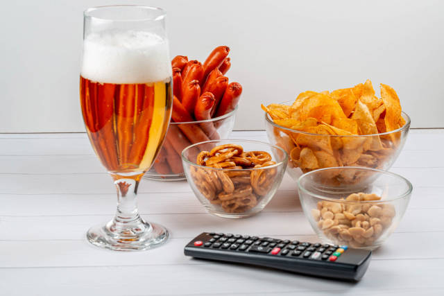 Beer, sausage, chips and peanuts with TV remote