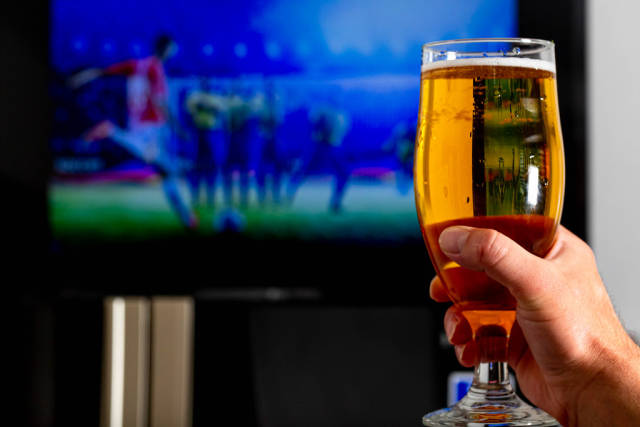 Hand with a glass of light beer on a blurred background of a football match