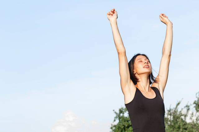 Yoga pose Urdhva Hastasana, girl stretching arms up in a standing position against the sky