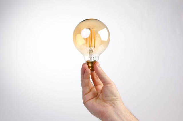 Hand holding lightbulb against white background