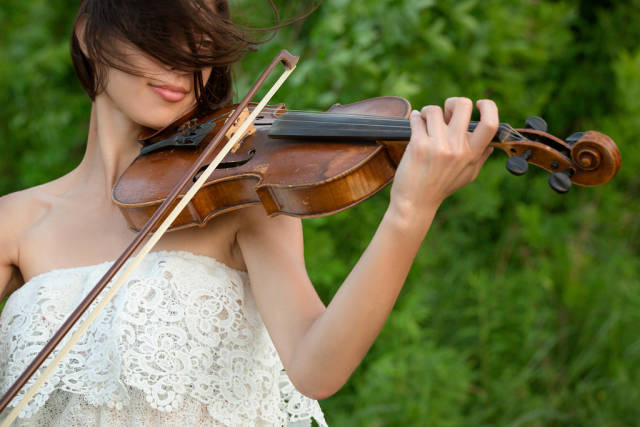 Young female violinist portrait on nature