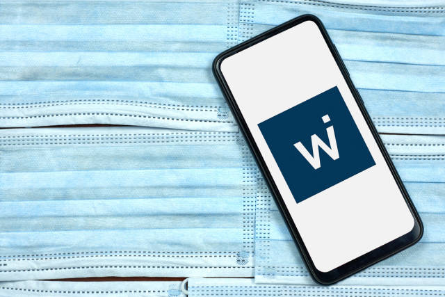 Wirecard logo displayed on smartphone over the face masks
