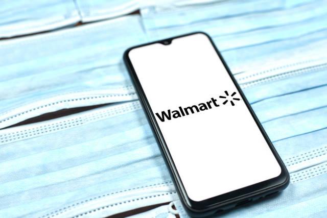 Walmart logo on smartphone screen over the face masks. Global company during coronavirus crisis