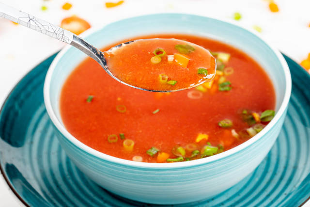 Tomato soup with herbs in a spoon