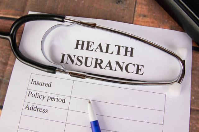 Krankenversicherungsformular mit einem Stethoskop und einem blauen Stift auf Holztisch