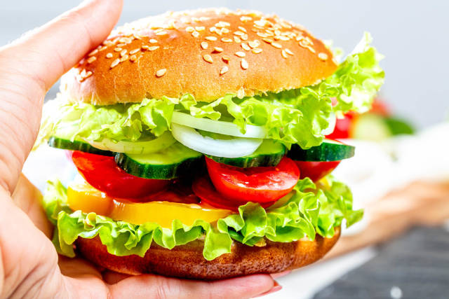 Hand hält vegetarischen Burger mit Salat, Gurken, Tomaten und Zwiebeln