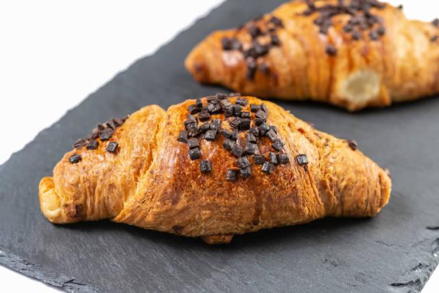 Croissantgebäck mit Schokoladendrops verziert, auf einem schwarzen Bretten aus Naturschieferstein