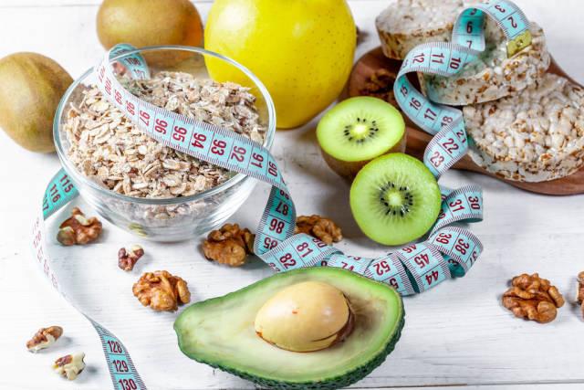 Gesundes Essen zum Abnehmen mit Haferflocken, Reiswaffeln, Avocado und Früchten mit Maßband