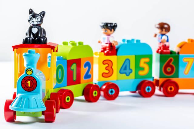 Bunter Spielzeugzug mit aufgedruckten Zahlen transportiert aufgesteckt e Katze und Kinderfiguren