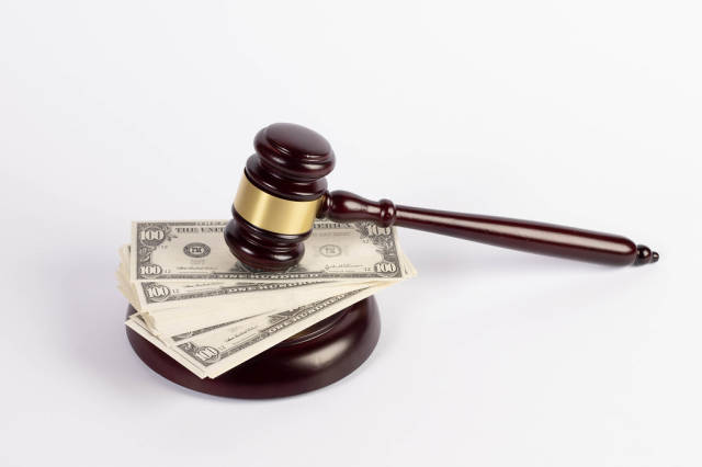 Richterhammer mit Geldscheinen vor weißem Hintergrund – Symbol für Korruption / Bestechung