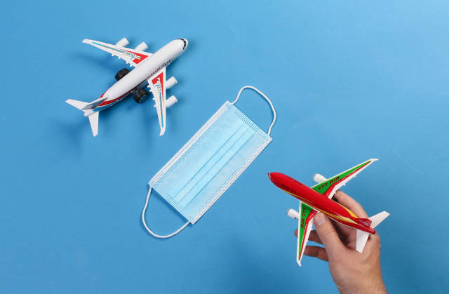 Toy airplanes with medical face mask on blue background