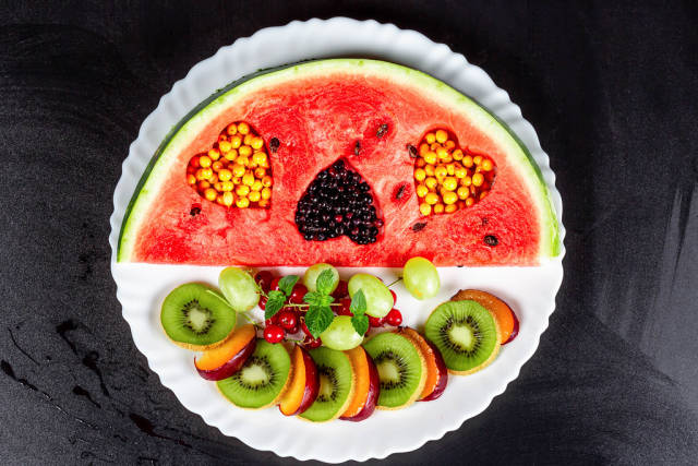 Fruit slicing on a white plate with berries on a black background