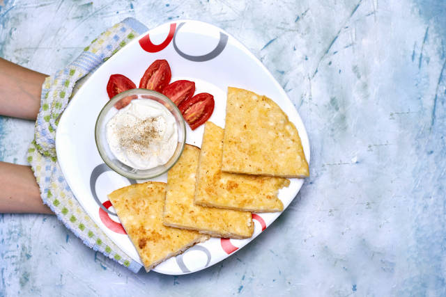 Woman holding rice-flour based khachapuri with a bowl of sour cream and fresh tomato slices