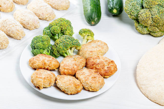 Chicken cutlets with fresh broccoli on a white plate
