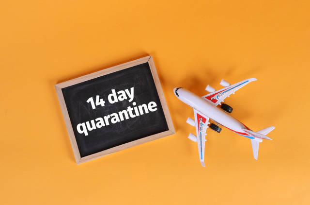 Airplane and blackboard with 14 day quarantine text on orange background