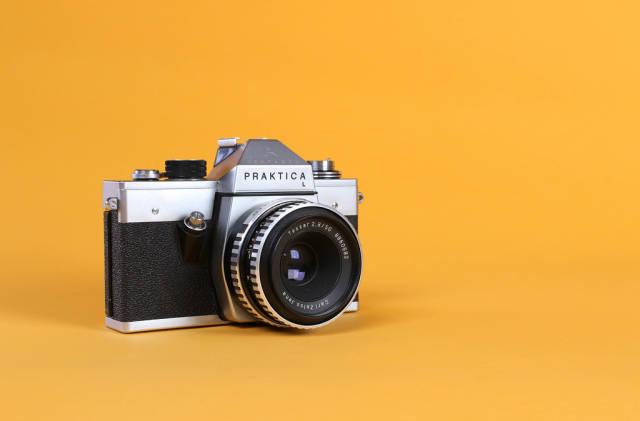 Vintage camera on orange background