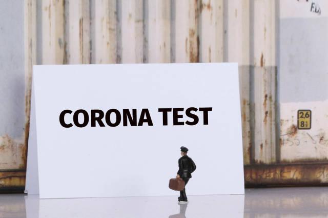 Corona Test - Mann mit Reisetasche steht vor einem Schild