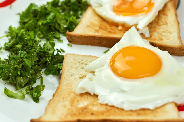 Fried eggs on the toasts. Delicious breakfast full with vitamins and nutrition