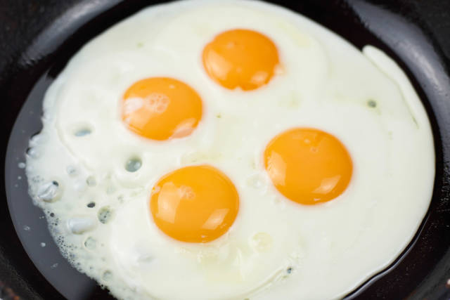 Four fried eggs in cast iron pan - sunny side up