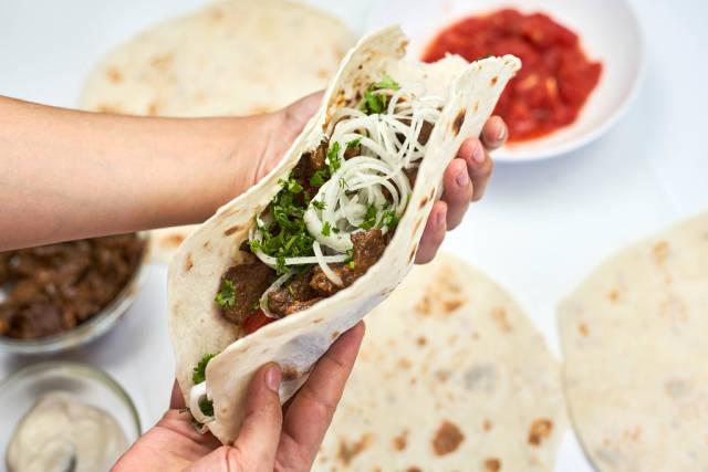 Woman preparing shawarma sandwich - roll of lavash filled with grilled meat, onions and sauce