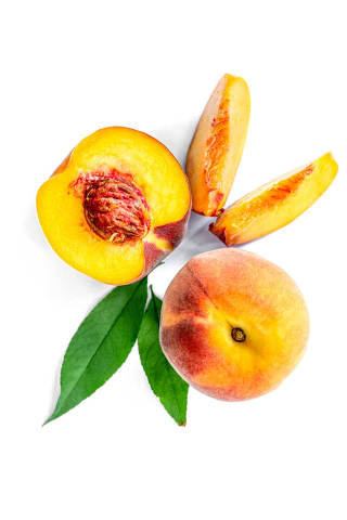 Whole, half and slices of peaches on a white background