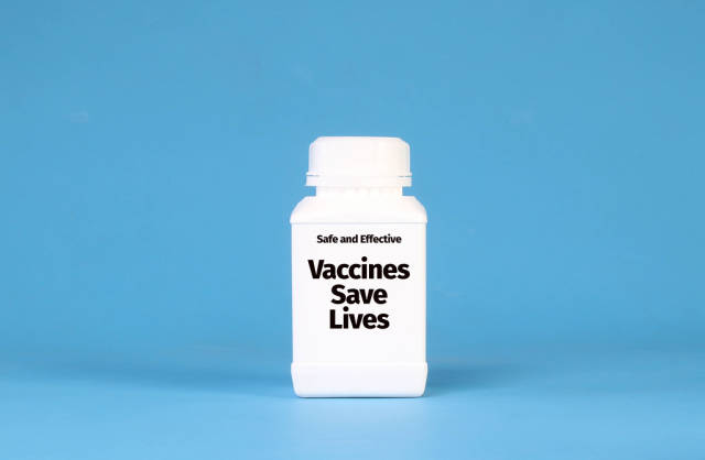 White bottle with Vaccines Save Lives text on blue background