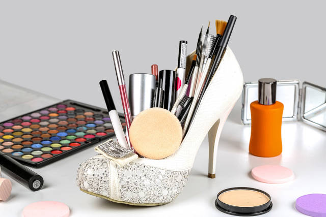 Set of different womens cosmetics with a white shoe