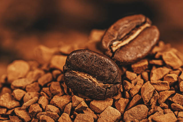 Close-up, roasted coffee beans on a mountain of instant coffee