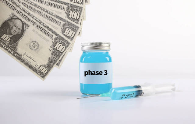 Bottle with Phase 3 text with money and syringe on white background