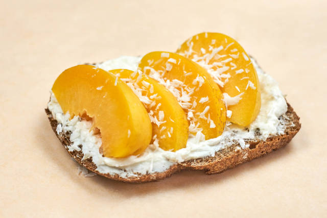 Close-up shot of sour cream spread on toast with peach slices