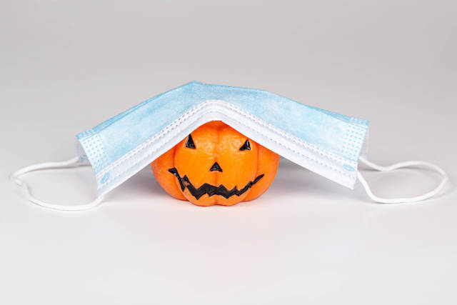 Concept Halloween , COVID-19 prevention. Pumpkin candle with medical mask