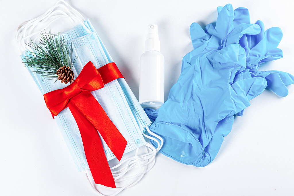 Hygienic face masks antiseptic and medical gloves with red ribbon, top view