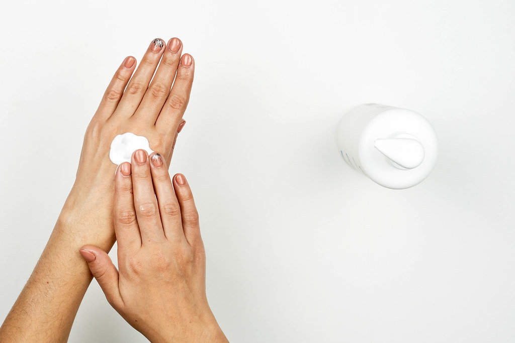 Woman hands massage rub cosmetic cream on white background